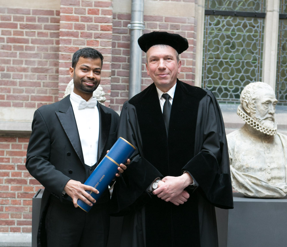 Dr. Biswajit Pradhan holding his degree certificate with supervisor Prof.dr. Michel Orrit in Leiden University's Academy Building